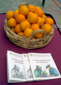 Coloring books and oranges, waiting for the start of the Museum Mile Festival.