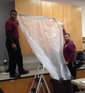 Facilities staff experiment with draping techniques to protect against a leak.