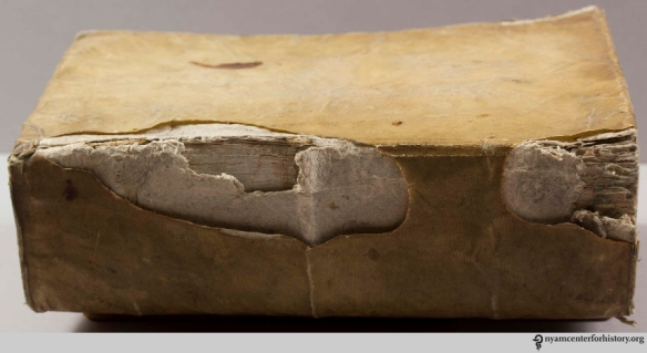 Wrapped board binding with inner paper board stiffener visible through damaged outer parchment cover. Lyon, 1641