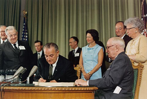 LBJ signs the Medicare Act (Social Security Amendments) with Harry Truman looking on, 07/30/1965. Courtesy of OurDocuments.gov.