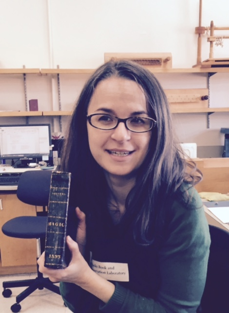 Book and Paper Conservator Christina Amato holds Demonomanie des Sorciers.