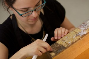 Christina Amato, cleaning old glue from the spine of a book.