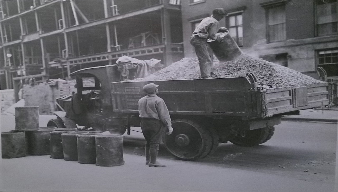 Two men hauling garbage into an open refuse truck.